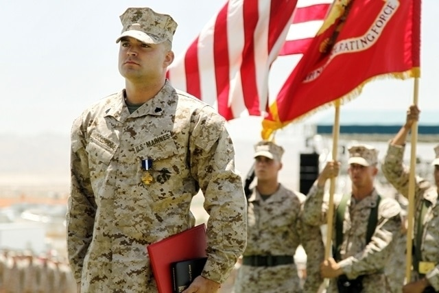 Sgt. Clifford Wooldridge, combat weapons instructor, Marine Corps Security Forces Regiment, Chesapeake, Va., stands at attention after receiving the Navy Cross Medal, May 18, at Lance Cpl Torrey L. Gray Field. He earned the medal for combat actions in Helmand province, Afghanistan, while attached to 3rd Battalion, 7th Marine Regiment, in 2010.