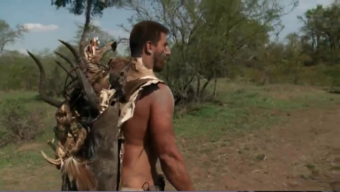 Matt Wright, carrying several big game skins and skulls. He spent 24 days surviving alone in Africa for Naked and Afraid X in 2018.