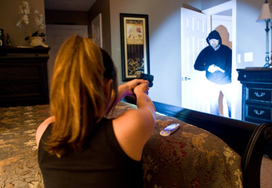 Armed woman at defensive position in room